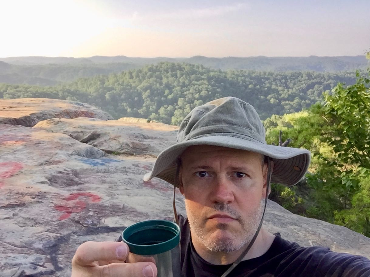 An image of photographer Michael Scott enjoying a cup of coffee on the summit of Lockegee Rock.
