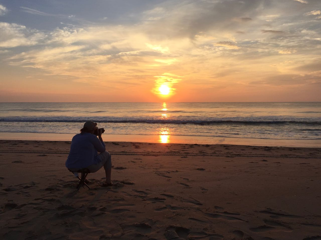 A woman photographing a sunrise on the beach while demonstrating an innovative method to capture a sharp image and reduce the effects of camera shake.
