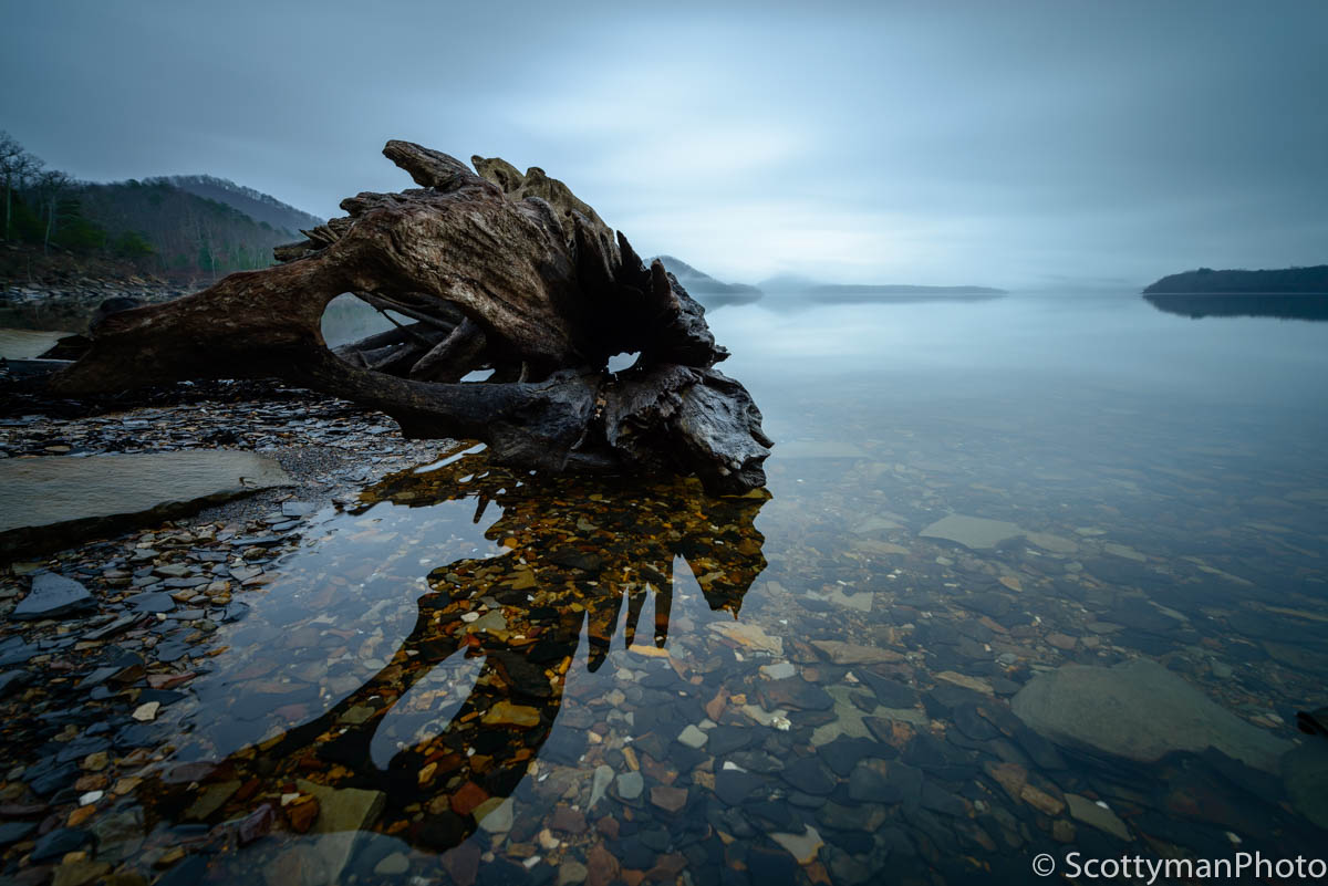 An example of what Is fine art photography by Michael Scott. An early morning sunrise at Cave Run Lake with fog covered mountains and a large piece of driftwood in the foreground.