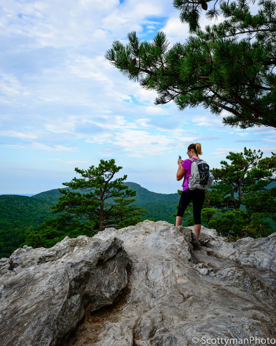 An image of a woman taking a picture with her smartphone while at Hanging Rock State Park in North Carolina.